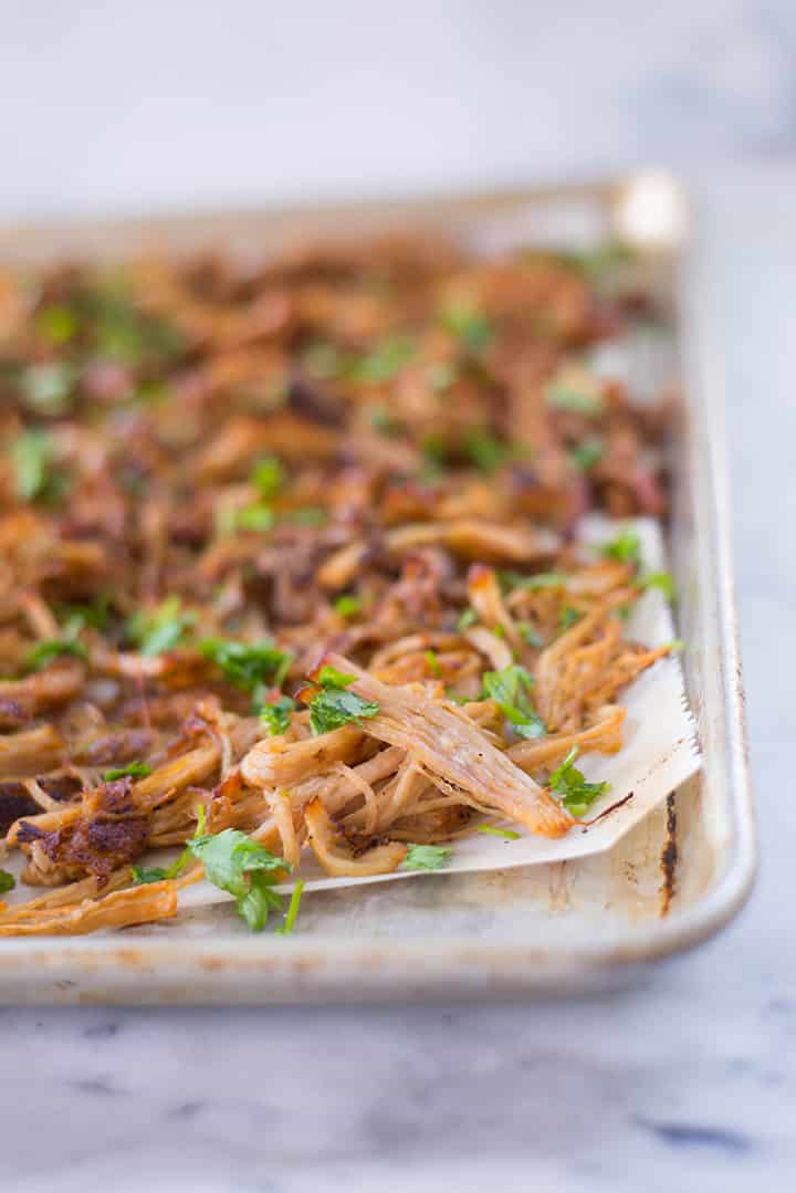 Carnitas pulled pork topped with cilantro on a baking tray.
