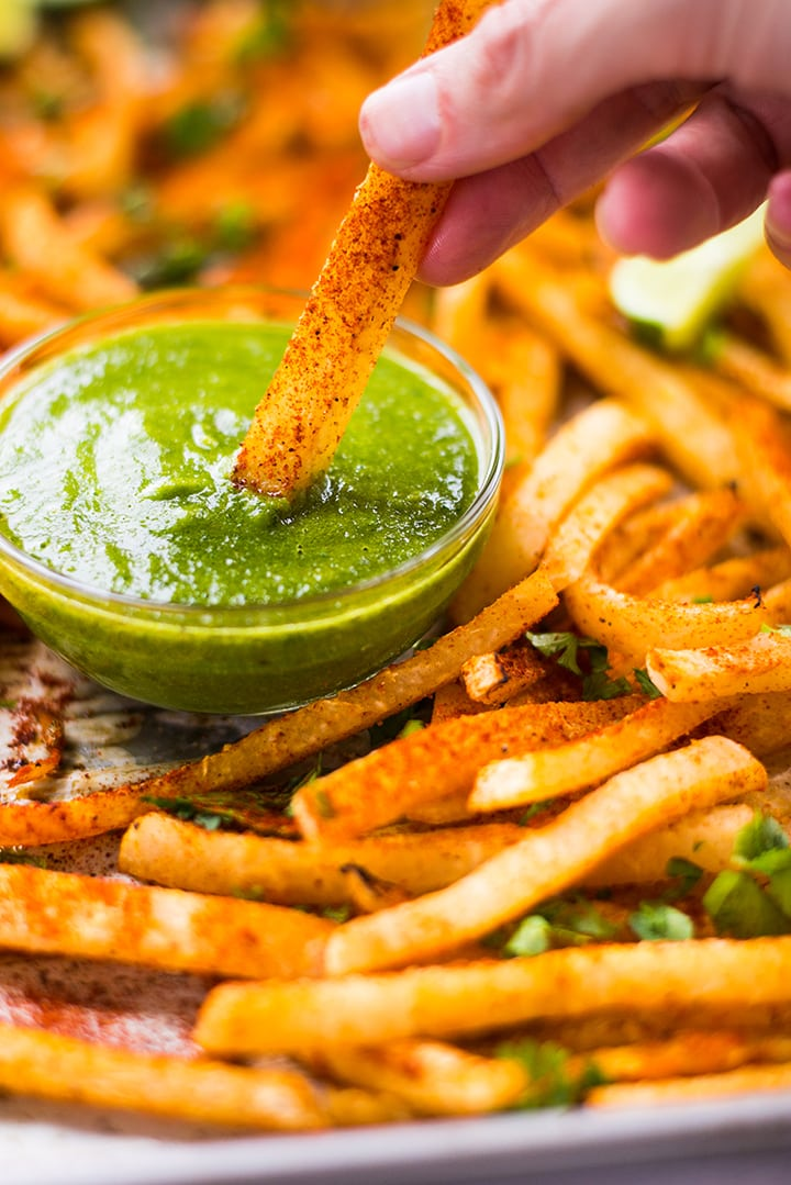 Close up of jicama fries. Lacey is dipping one fry into the chimichurri dipping sauce.