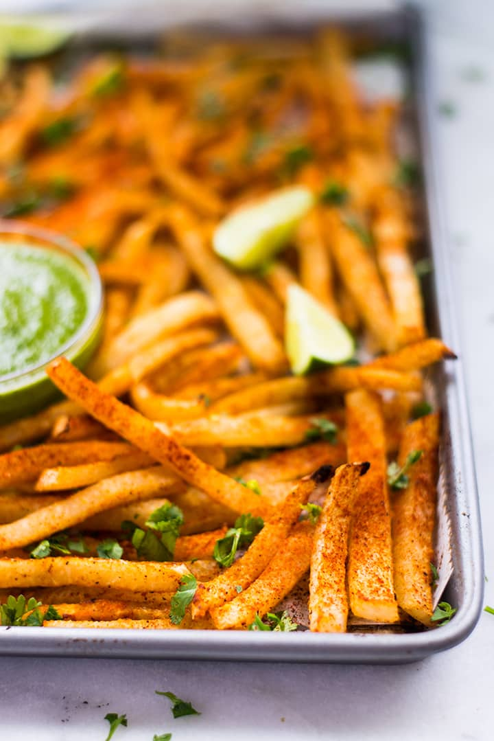 Freshly bakes jicama fries garnished with parsley on a baking sheet.