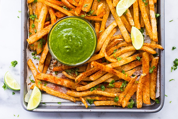 View from the top of the baking sheet with the jicama fries. The jicama fries were garnished with fresh parsley and lemon slices and in the middle of the baking sheet is the chimichurri dipping sauce.