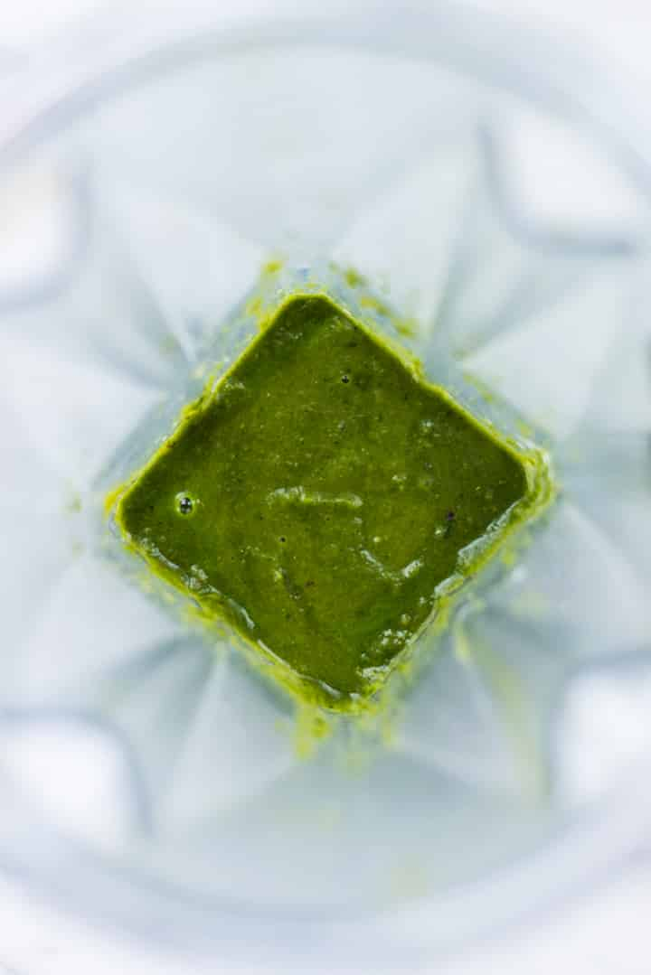 The chimichurri sauce made with parsley, cilantro, red onion, jalapeno, lime juice, garlic, salt, cumin, and coriander seeds in a blender. The chimichurri sauce will be served as a dipping sauce for jicama fries.