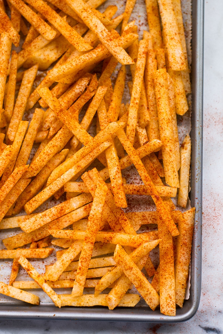 Jicama fries seasoned and spread on a baking sheet ready to be transferred to the oven to bake.