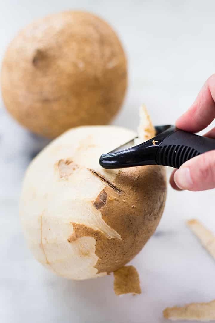 Lacey peeling jicama with a vegetable peeler.