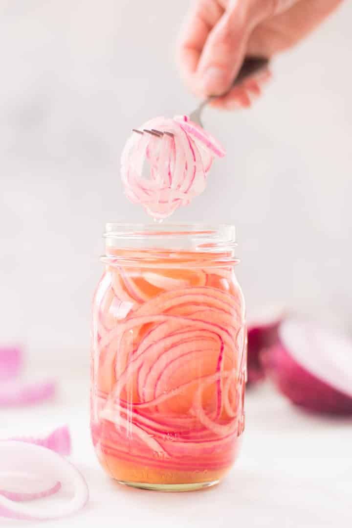 Side view of mason jar filled with pickled red onion.