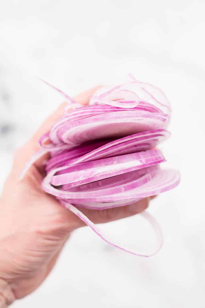 Lacey holding thin slices of red onion in her hand.