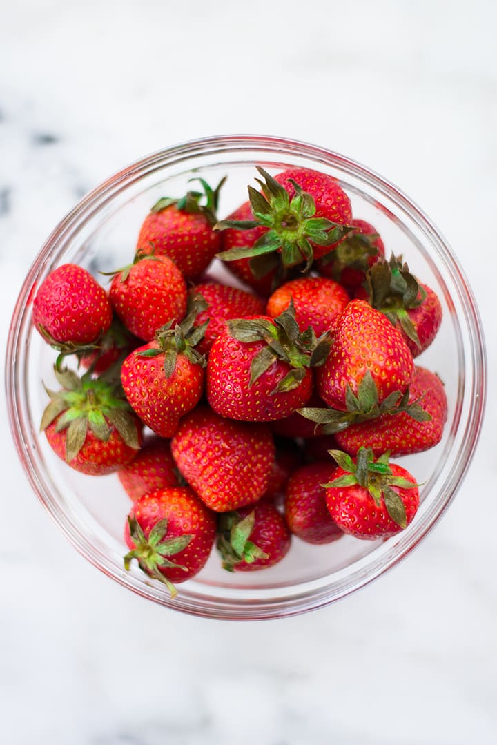 Overhead view of a glass bowl filled with strawberries, a fiber-rich food.