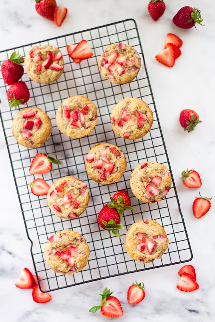 Top view of the strawberry muffins on the cooling rack. The cooling rack is surrounded by fresh strawberries and fresh strawberries cut in half.