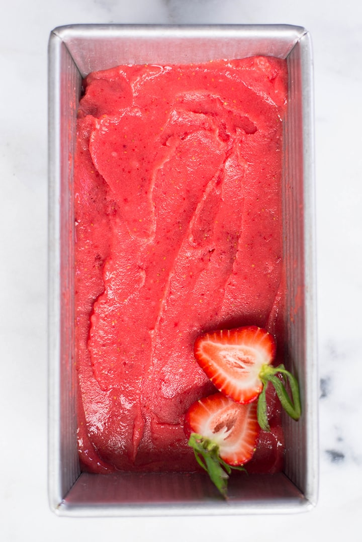 View from the top of homemade strawberry sorbet in a loaf pan.