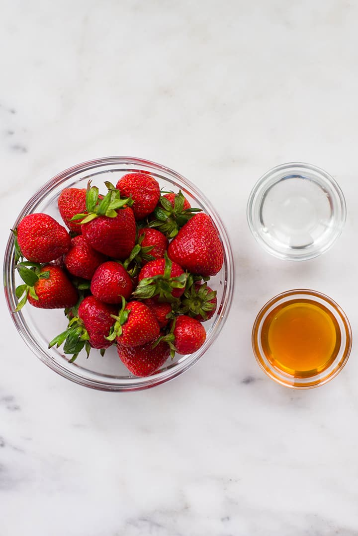 Separated ingredients for strawberry sorbet including fresh strawberries, raw honey, and warm water.
