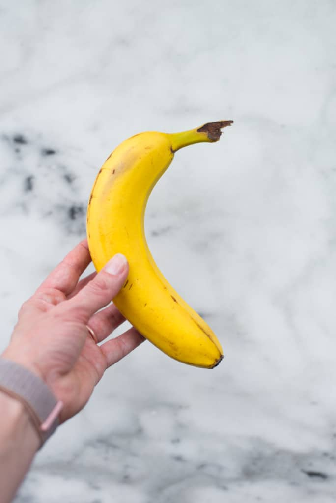 Hand holding banana for example of cutting calories to excess for 12 Weight Loss Mistakes