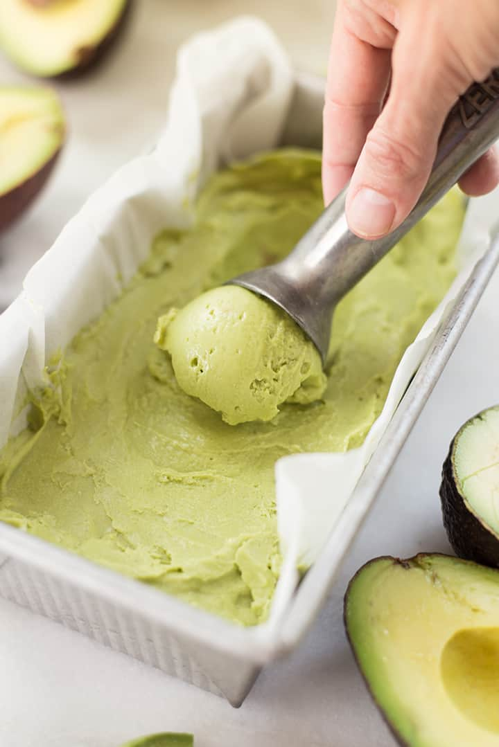 Hand rolling a scoop of avocado ice cream in a freezer-safe container, ready to be served.
