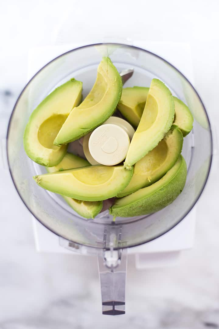 Bowl of food processor filled with fresh, sliced avocados, ready to be processed and used in the avocado ice cream recipe.