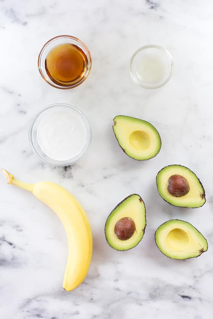 Simple ingredients for the avocado ice cream, including avocado, banana, coconut milk, raw honey, and fresh lemon juice.