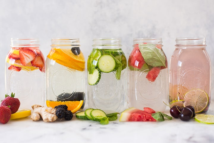 5 flavors of infused water in mason jars lined up in a row, including strawberry banana and cucumber.