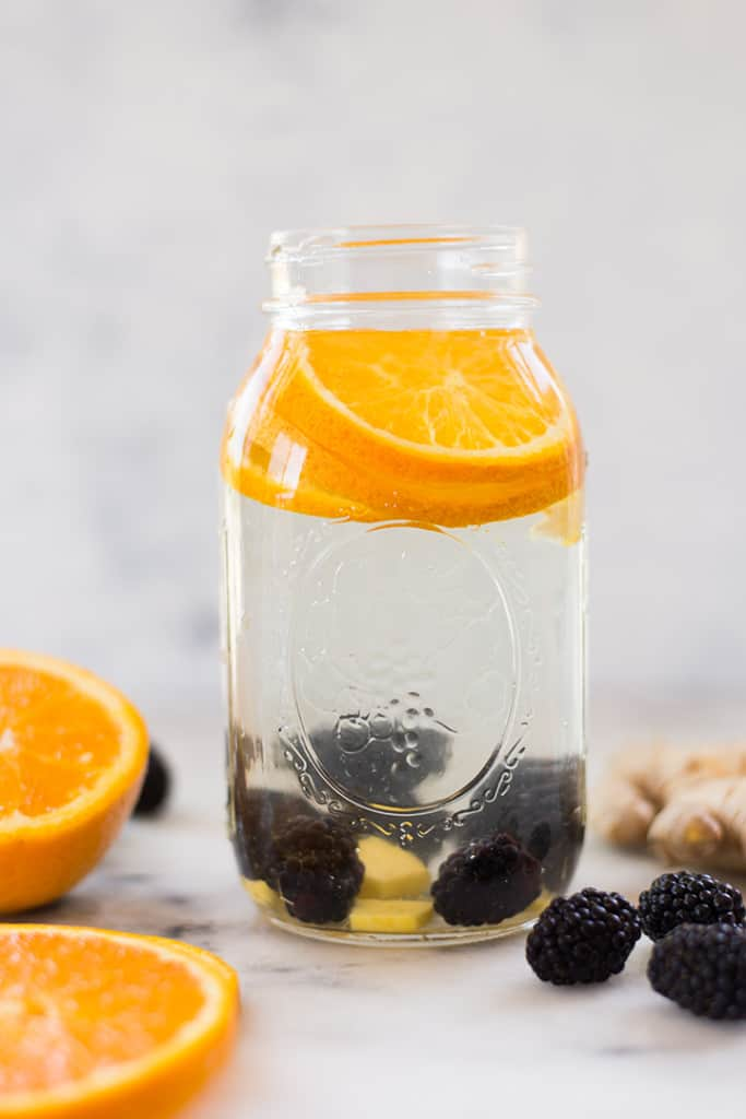 1 quart mason jar filled with blackberries, orange, ginger, and water for infused water, ideal for drinking when in an eating window of the Intermittent Fast.