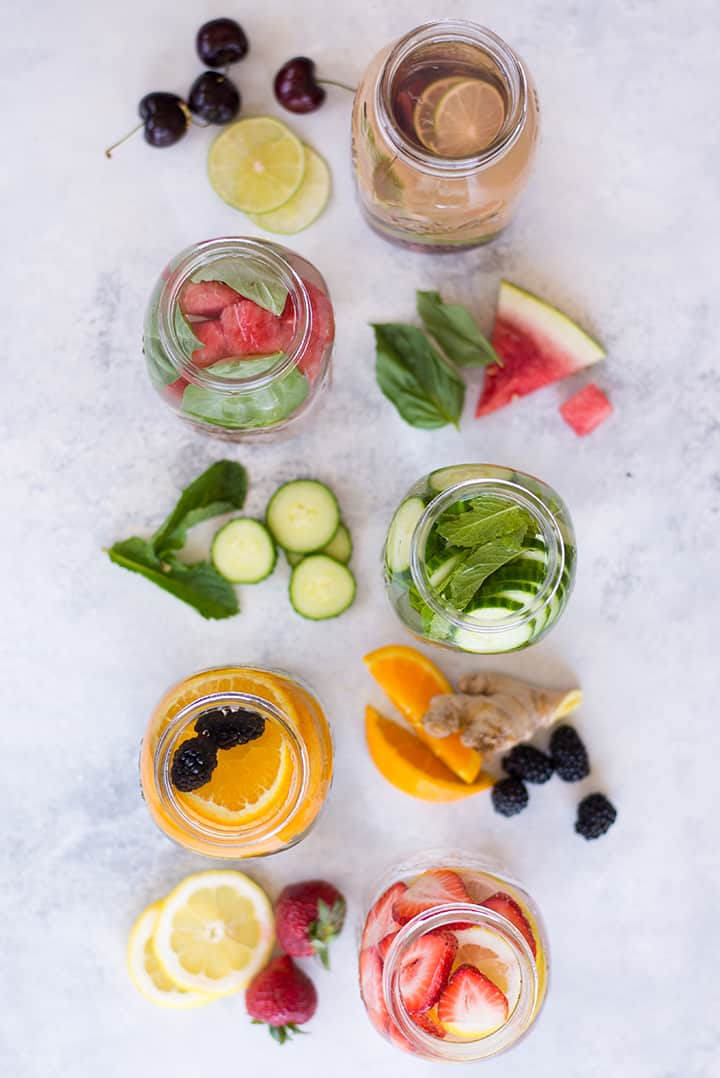 Overhead view of 5 mason jars with ingredients for different infused water recipes., including oranges, lemons, and cucumbers