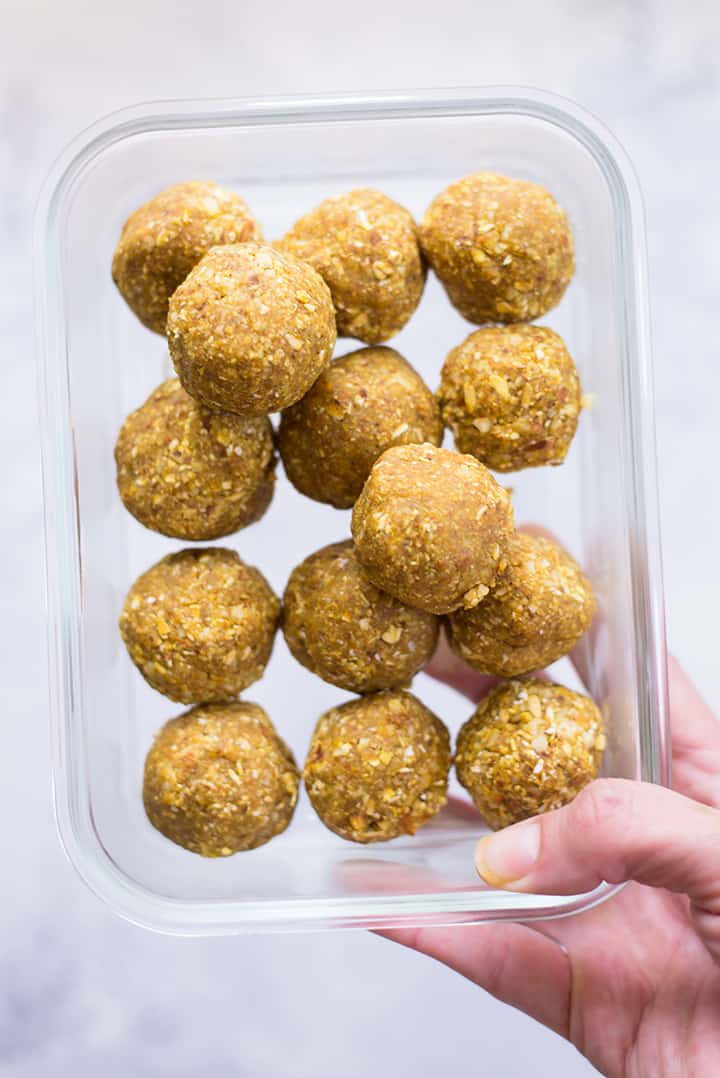 Hand holding meal prep container with the lemon turmeric energy balls which are the snack for the meal plan to reduce inflammation.