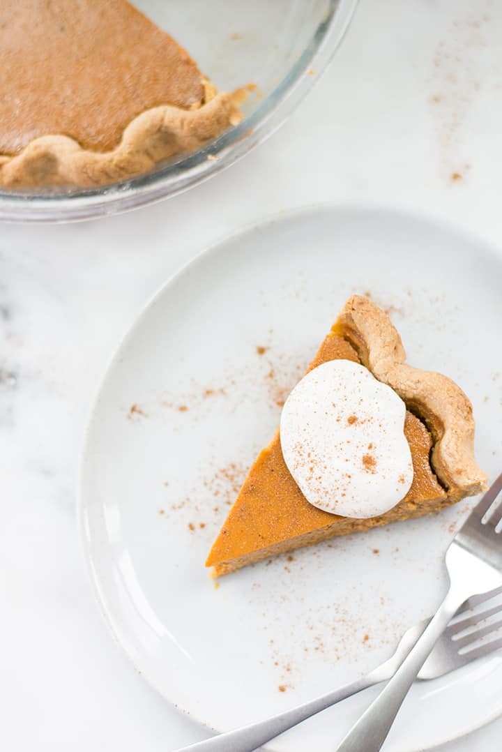 Overhead view of a slice of pumpkin pie from scratch topped with whipped cream from scratch and sprinkled with cinnamon.