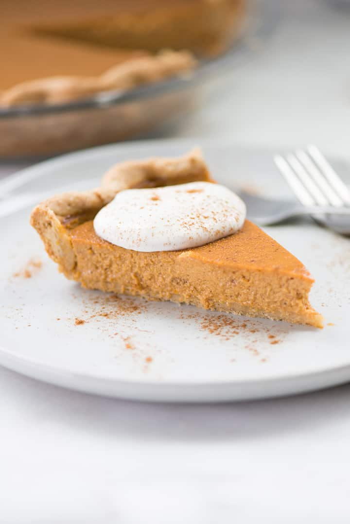 Close up shot of a single slice of pumpkin pie from scratch, topped with fresh vegan whipped cream and cinnamon.