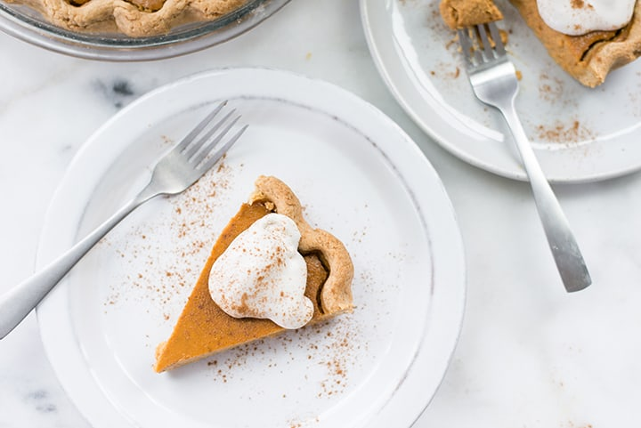 Overhead view of two slices of pumpkin pie, one has been slightly eaten, and both are topped with keto whipped cream and cinnamon.