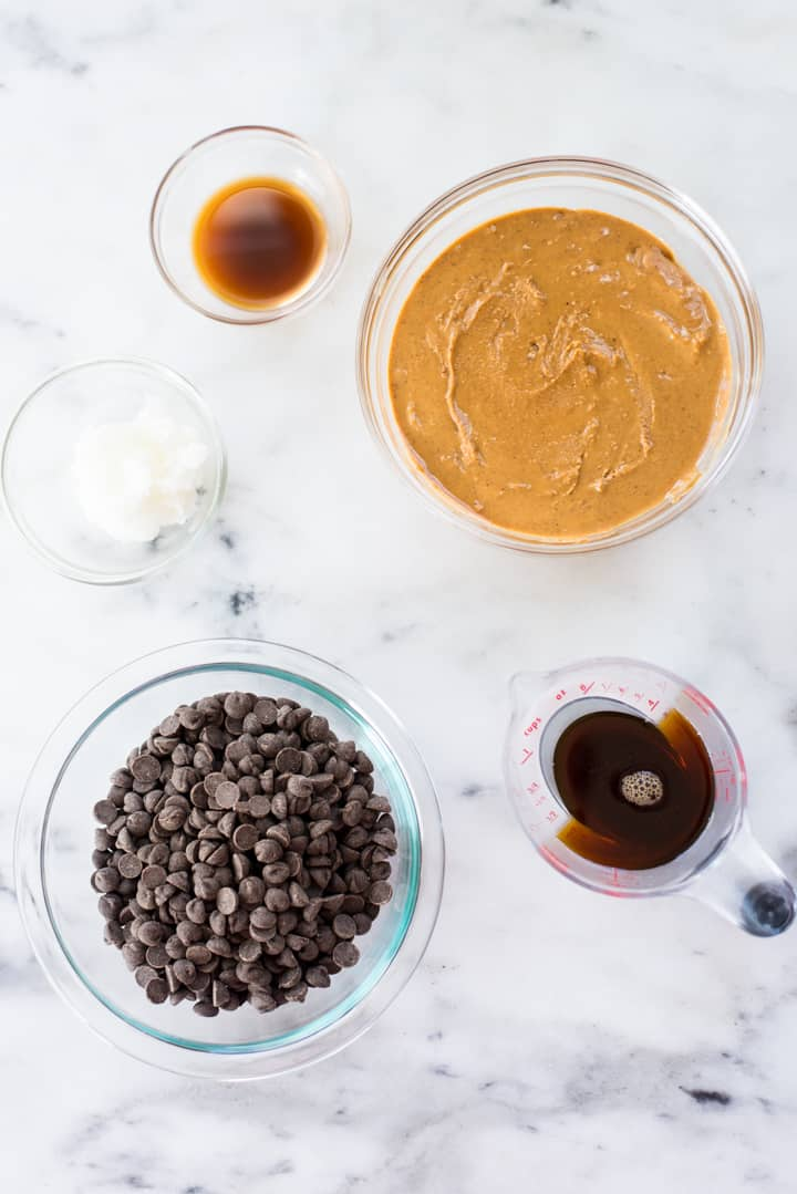 Overhead view of all the ingredients required to make the Easy Chocolate Peanut Butter Fudge, including natural creamy peanut butter, vanilla extract, coconut oil, dark chocolate morsels, and pure maple syrup.