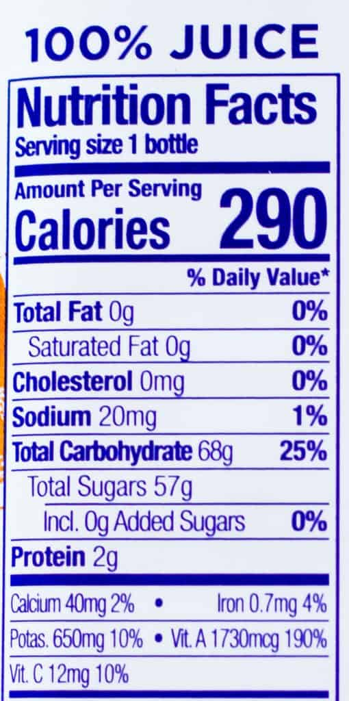 Overhead view of a fruit juice label showing the ingredients, including 57 grams of sugar.