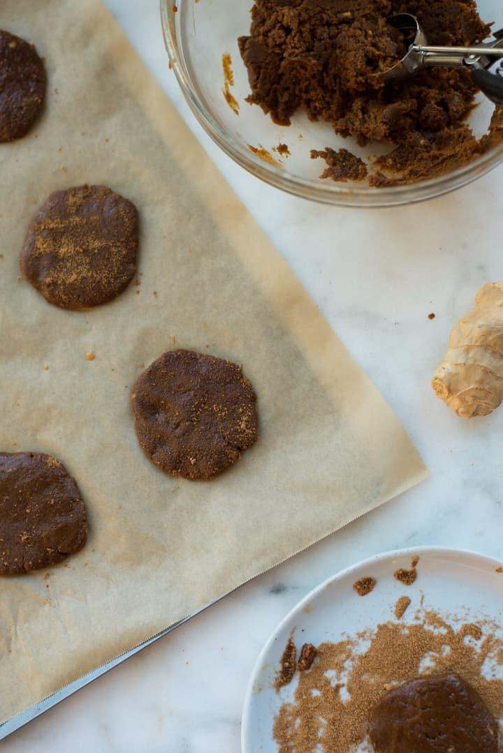 Draufsicht auf ein mit Pergamentpapier ausgekleidetes Tablett mit Keksen für gesunde Ingwermelasse, das zum Backen bereit ist