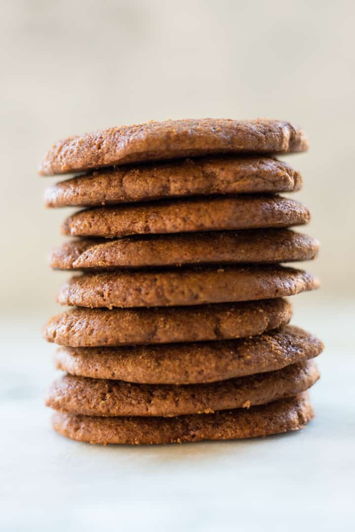 View of a tall stack of freshly baked Healthy Ginger Molasses Cookies, made with whole wheat flour.