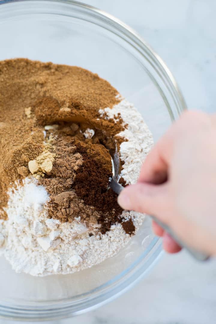 Ansicht des Mischens der trockenen Zutaten in einer klaren Glasschüssel für gesunde Ingwermelasseplätzchen