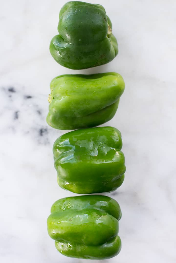 Overhead view of four large green peppers, to be used in Keto Philly Cheesesteak Stuffed Peppers | Keto Meal Prep