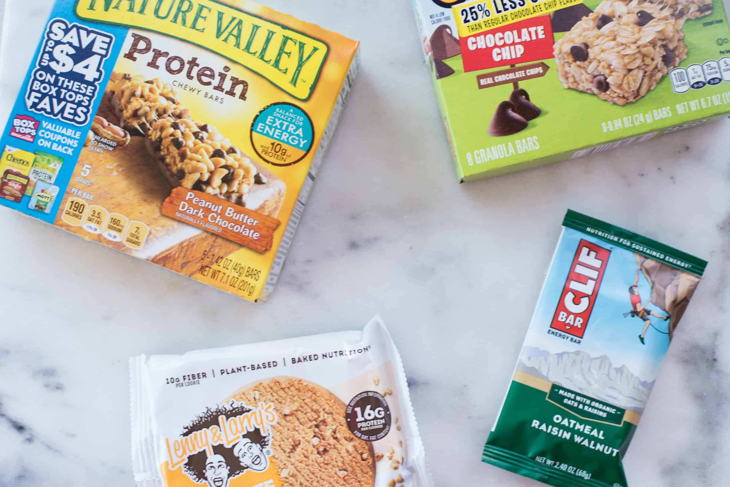 Overhead view of packaged foods that may contain saturated and trans fats, such as cookies and granola bars.