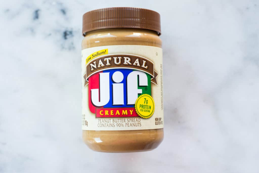 Overhead view of a jar of sweetened peanut butter, which has sugar and hydrogenated oils.