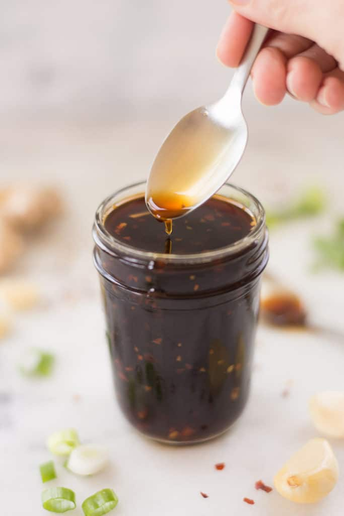 Side view of a glass jar filled with the best healthy teriyaki sauce, with a spoon dipping into the sauce.