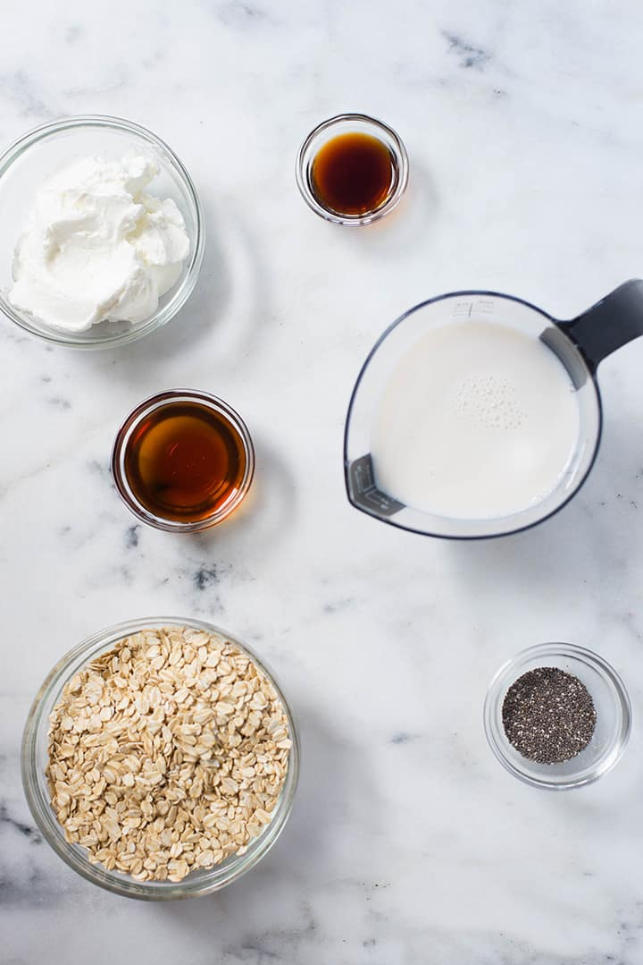 Overhead view ingredients used in Chocolate Peanut Butter Overnight Oats, including rolled oats, chia seeds, almond milk, pure maple syrup, vanilla, and plain Greek yogurt.