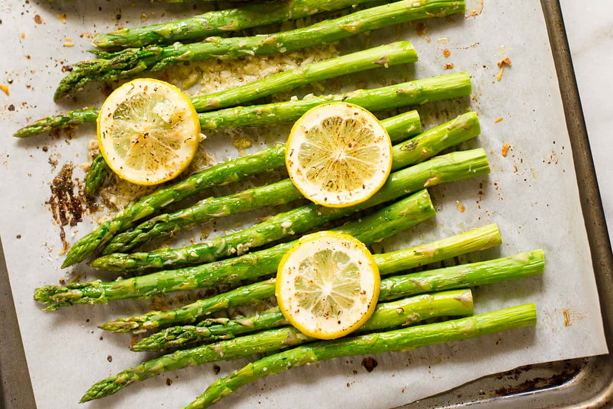 Close up view of a parchment paper lined sheet pan with baked asparagus topped with lemon slices.