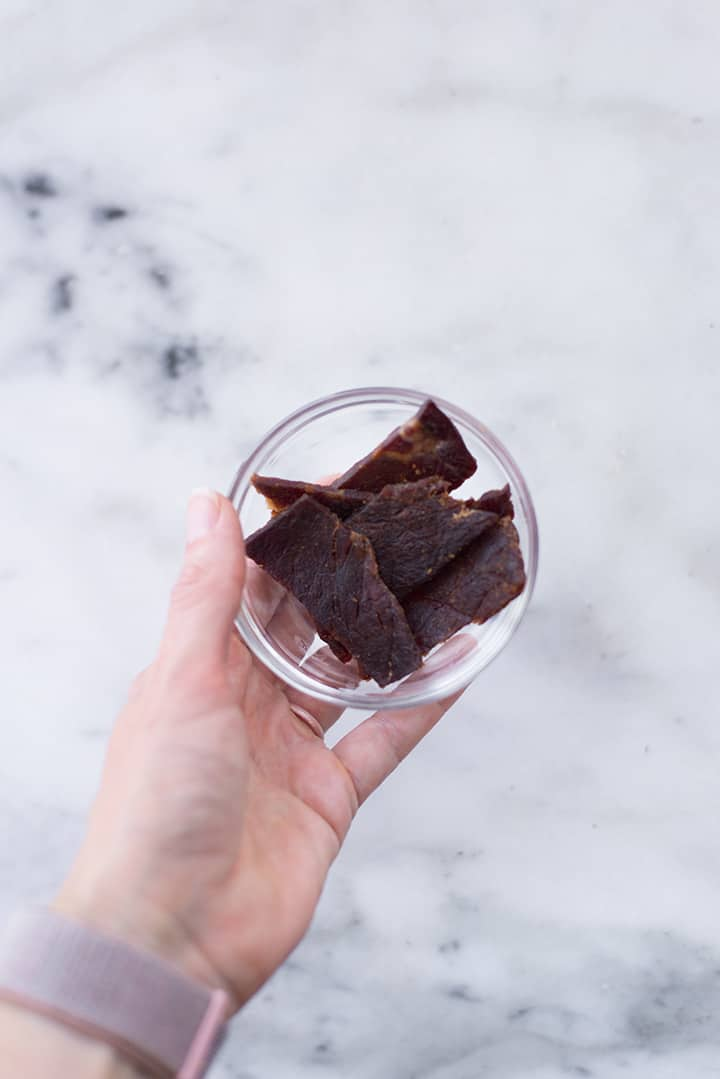 Overhead image of a hand holding a small glass bowl containing beef jerky.