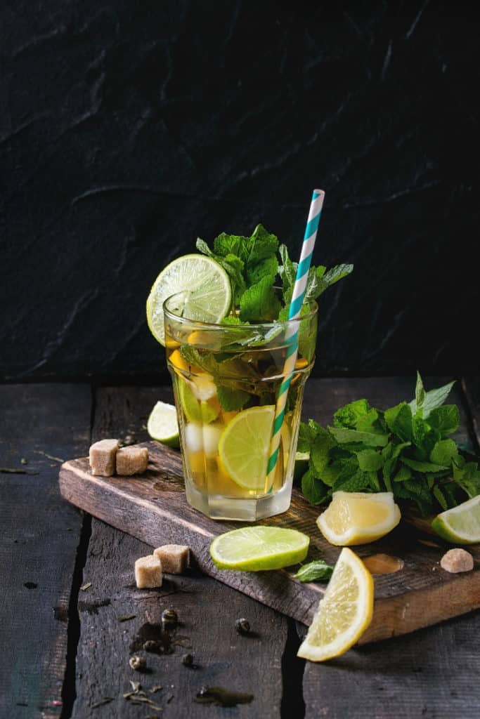 Close up image of a tall clear glass filled with green tea, with lemons, limes, and mint around the glass.