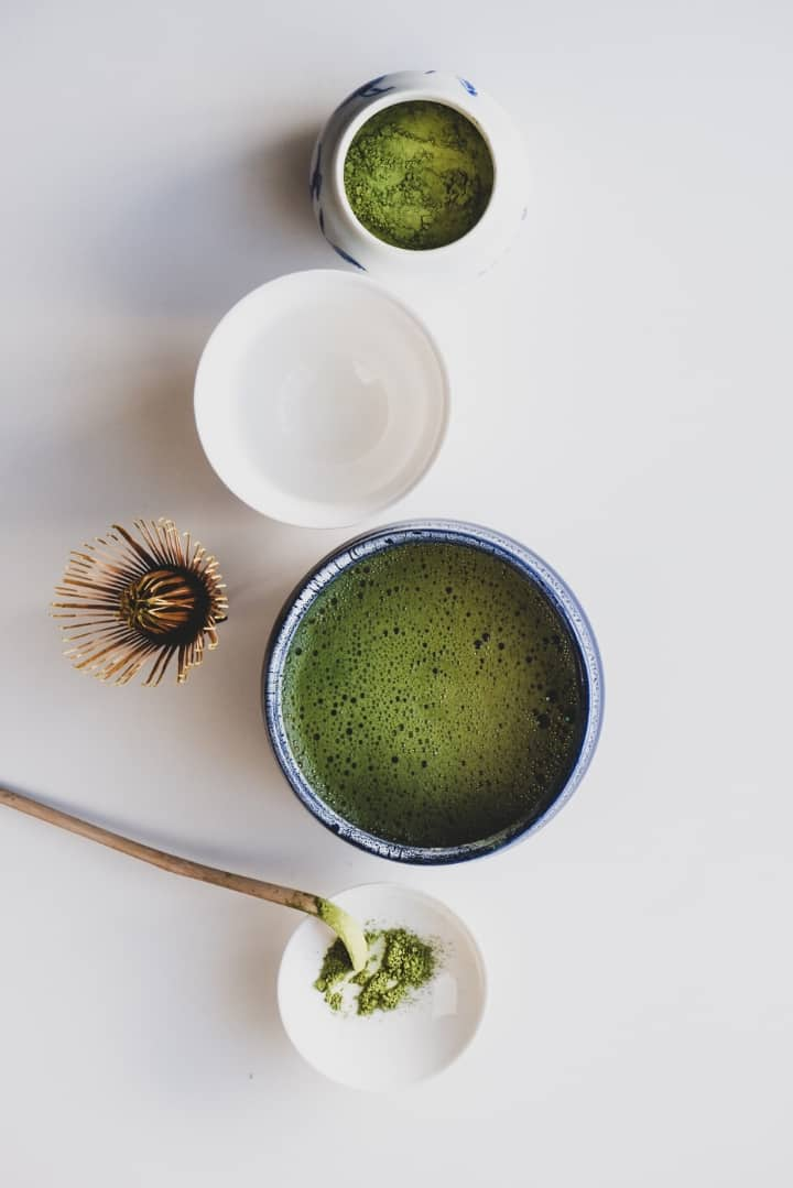 Overhead view of green tea powder in a small ceramic container as well as green tea prepared and ready to drink.