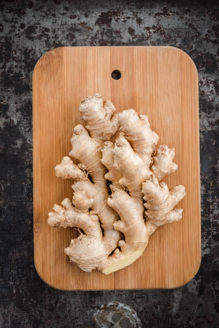Overhead view of several ginger rhizomes placed on a dark wooden cutting board, ready for slicing.