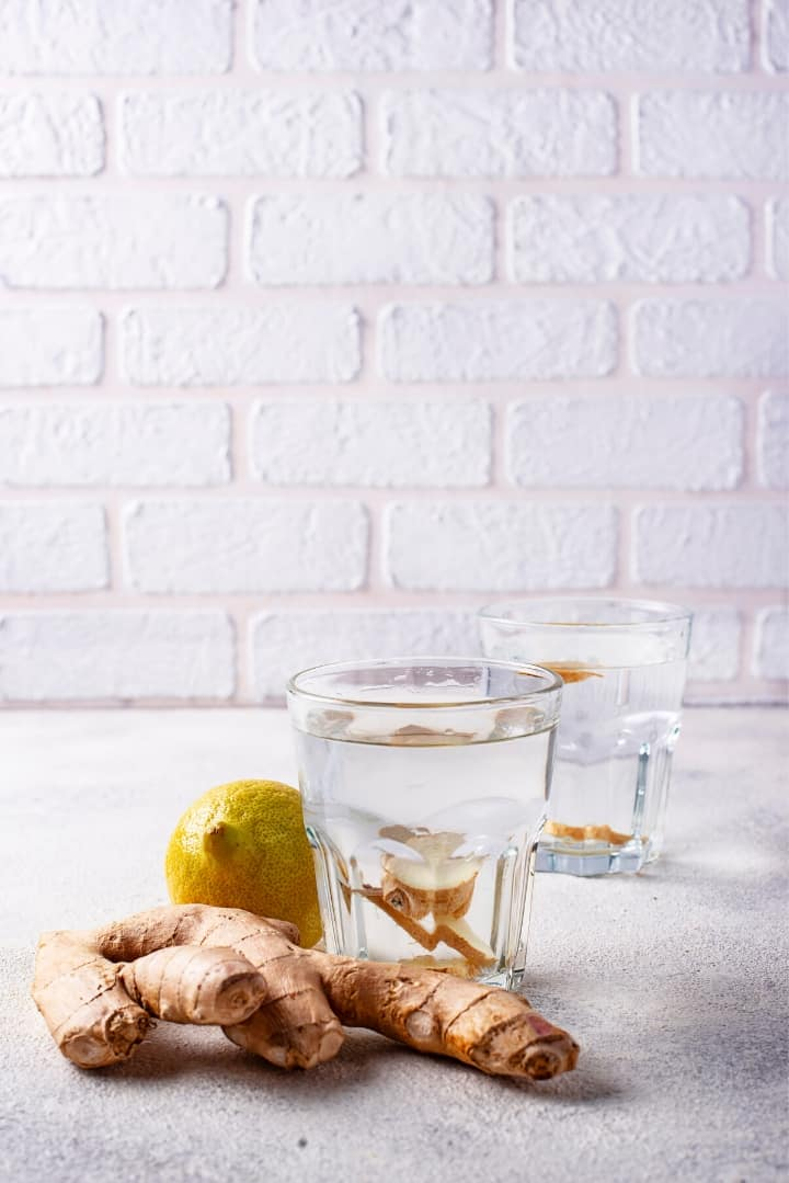 Side view of two glasses of water containing ginger pieces beside an uncut ginger rhizome and a lemon.