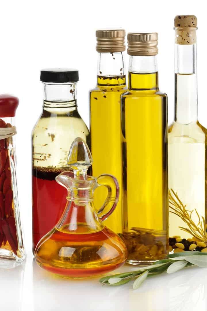 Close up image of six glass bottles of varying sizes, filled with different types of oil.