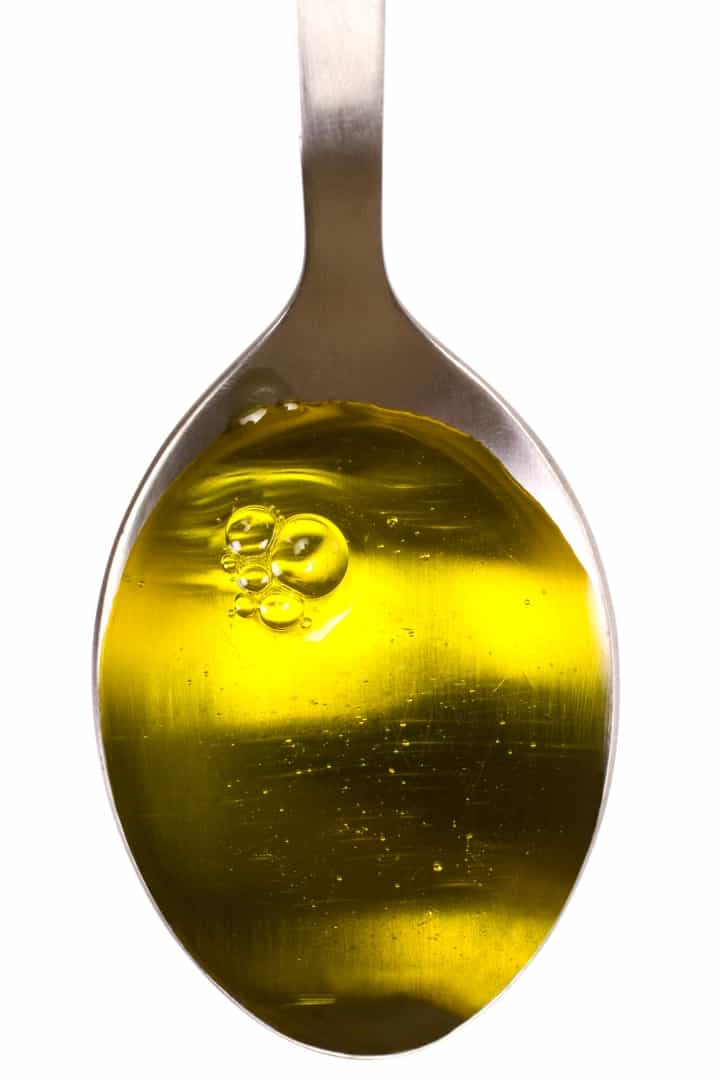 View of a spoon filled with a cooking oil, measured and ready to be used in a recipe.