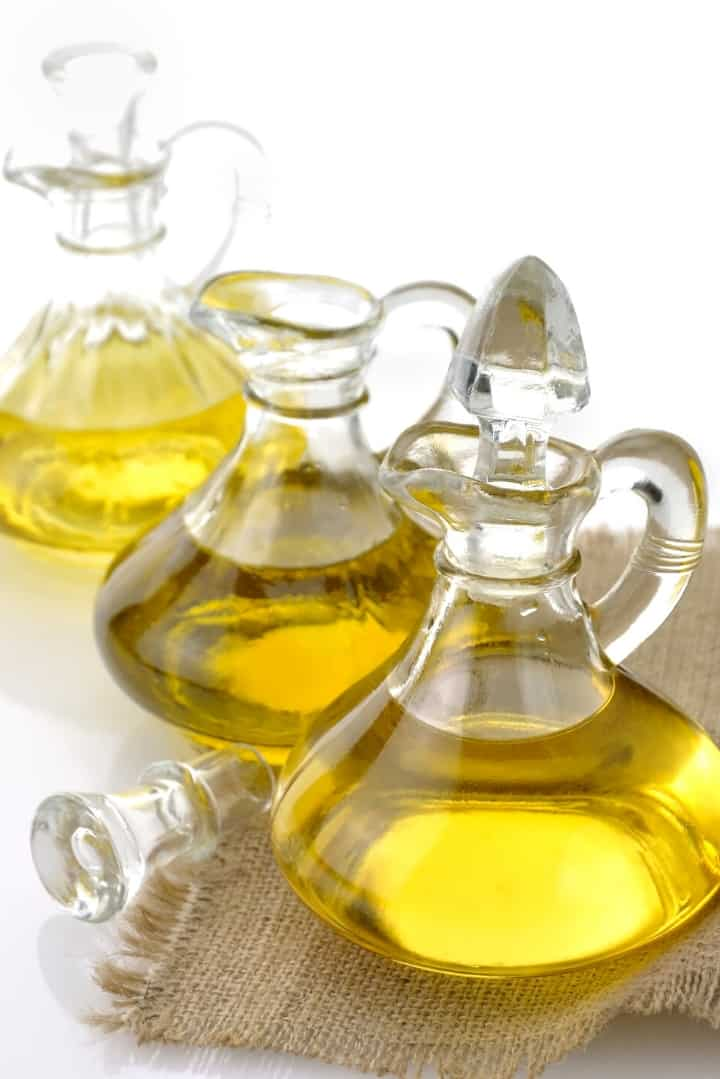 Close up image of 3 glass bottles of cooking oil, one with the top open, placed on a woven place mat.