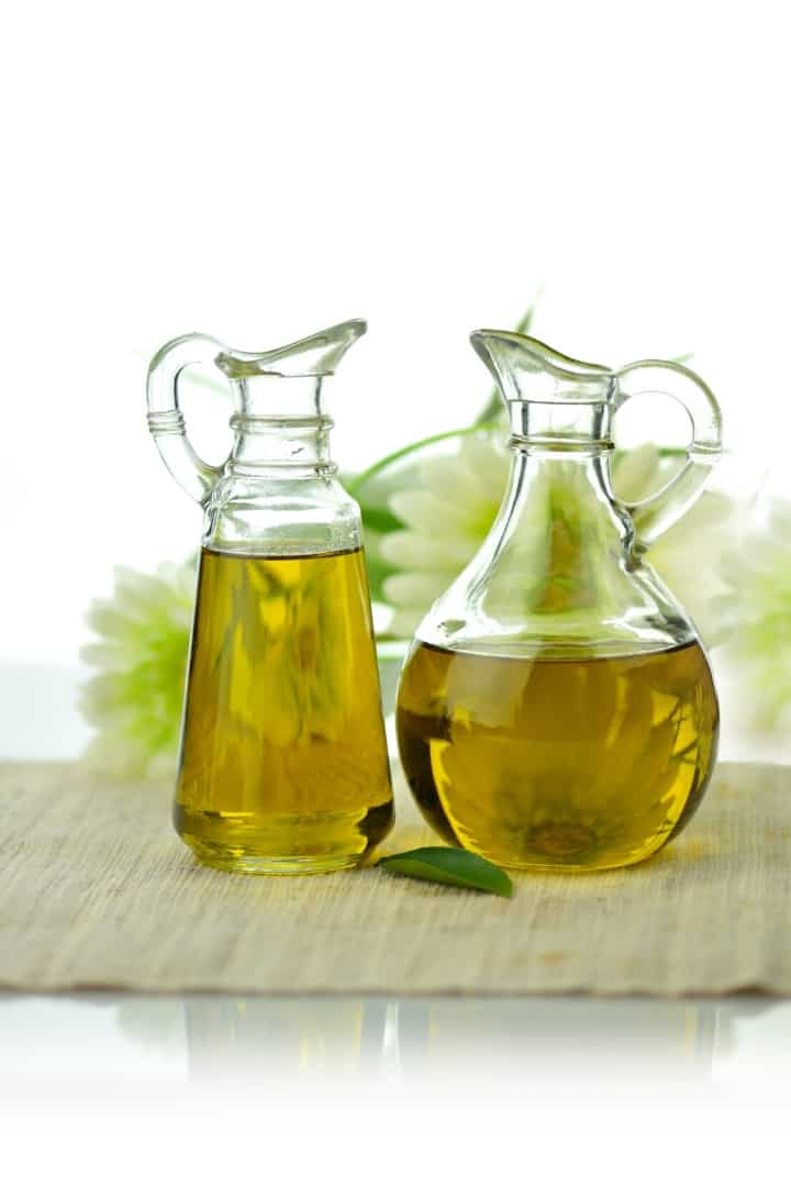 Close up side view of two glass bottles of healthy oil, sitting on a woven place mat.