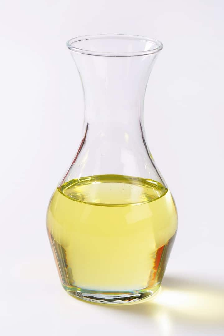 Close up view of a shaped glass bottle, half full of cooking oil.