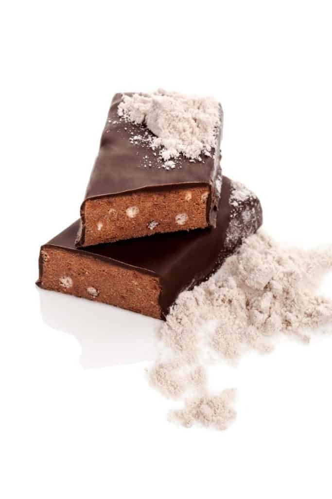 Close up side view of a chocolate protein bar sliced in half and the pieces stacked on each other.