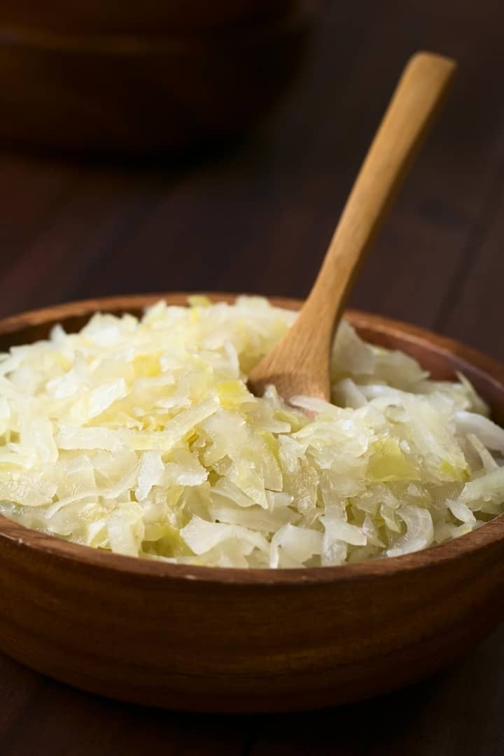 Close up view of a wooden bowl filled with sauerkraut, with a wooden spoon in the bowl.