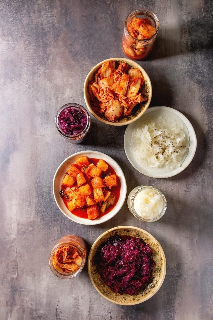 Overhead image of eight bowls containing fermented foods, to include purple cabbage sauerkraut, sauerkraut, and onions.