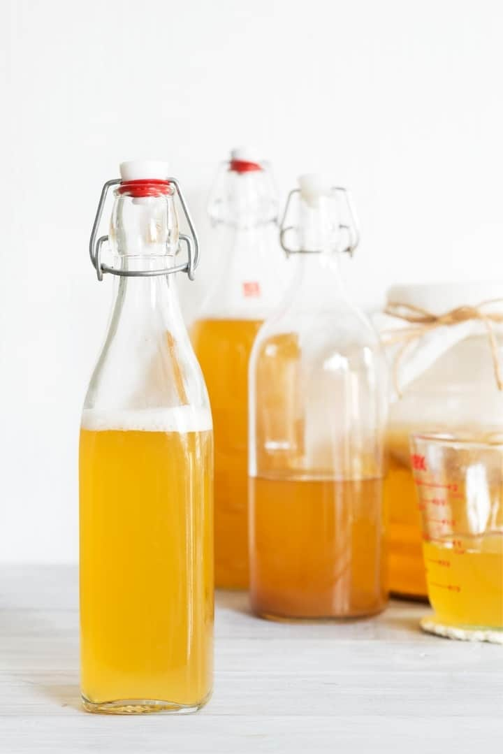 Close up image of bottles and a measuring cup, containing apple cider vinegar, a good for you fermented food.