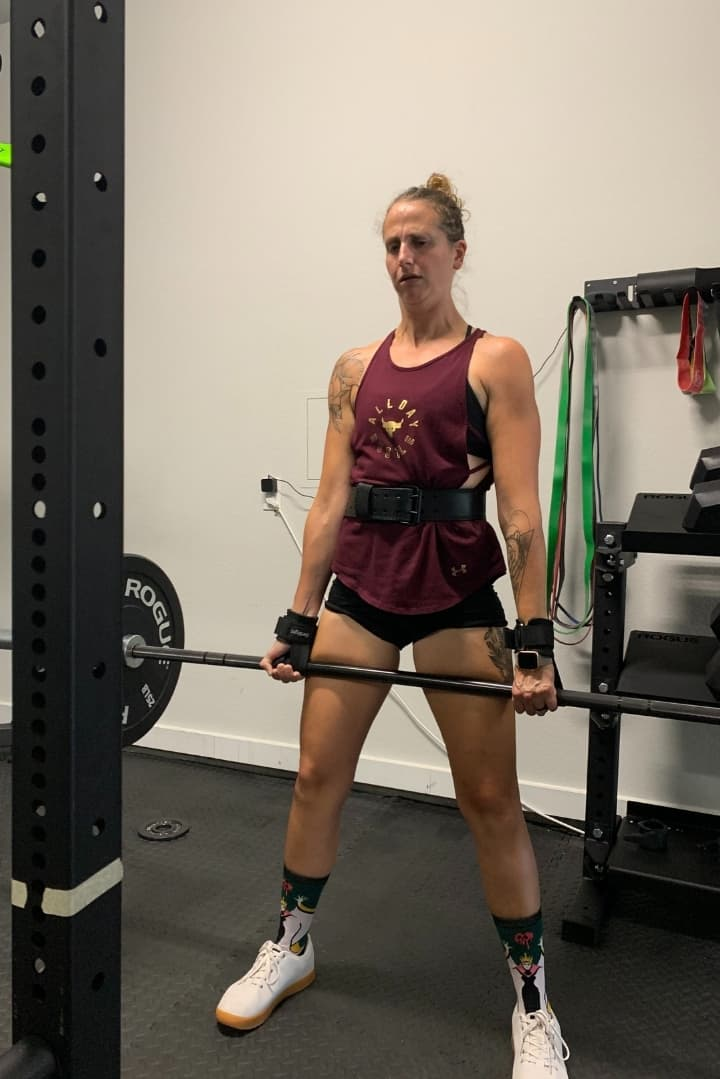 Close up image of Lacey in workout gear, lifting a barbell as part of a weight lifting workout.